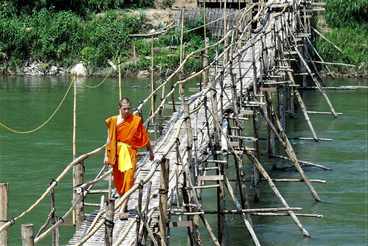 Monk rossing bamboo bridge Luang Prabang