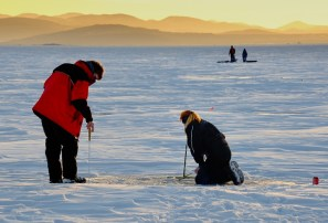 Ice fishing on Lake Champlain, late in the day—a young man and woman tend to their holes.