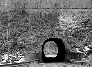 A railroad passes over a small county road. A one-lane culvert serves to funnel traffic under the tracks.