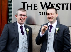Newly married, with his best man, enjoy a cigar after the wedding. The groom is on the left, and he looks happy.