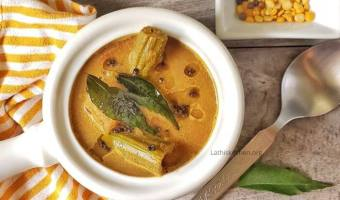 Bowl of Kerala Varutharacha sambar with a spoon, curry leaf and pepper on side.
