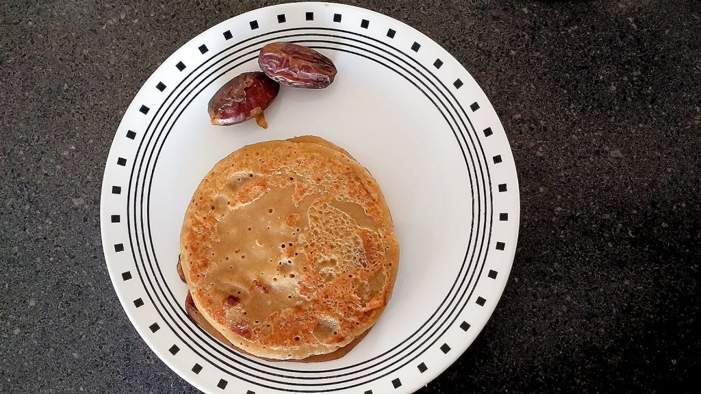 A plate of Whole wheat Banana Dates Pancake with dates on side.