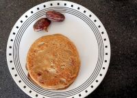 A plate of eggless whole wheat dates pancake with dates on side.