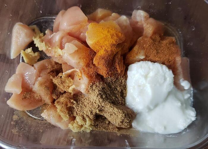 Chicken marinating with yogurt and spices in a bowl.