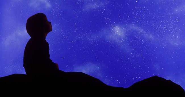 Square image of a small child in profile looking up at a star filled night sky