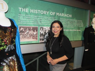 Dr. Leonor Xóchitl Pérez - in front of the exhibit she brought to Denver for the world premier of American Mariachi. Xóchitl Pérez is the Director and Founder of the Mariachi Women's Festival, Dr. Leonor Xóchitl Pérez began performing mariachi music in the 1970's at Griffith Junior High School which is located in East Los Angeles, California.