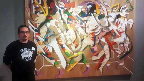 Artis tDiego Rodriguez-Warner in front of one his works inspired by Navajo influences. Photo by Latin Life Denver Media