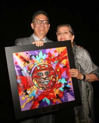 Rudy Gonzales & Lucille Rivera hold up the awards art work by Joaquin Gonzales II