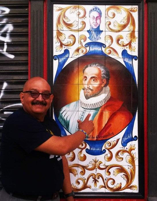 Author Silvio Sirias in front of a depiction of Miguel de Cervantes in Madrid.