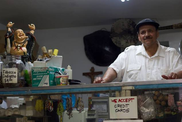 """Jorge """"Justo"""" Vargas behind the counter of his iconic botánica in Spanish Harlem (Photo Credit: Andrew J. Padilla)"""