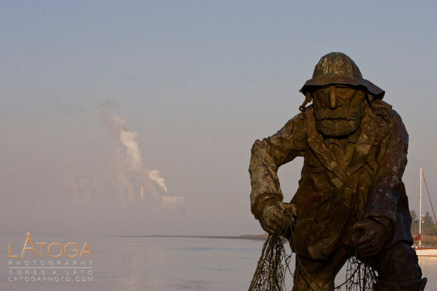 Sunrise Over Old Fisherman Statue and Fog Shrouded Power Plant at Humboldt Bay in Eureka, California