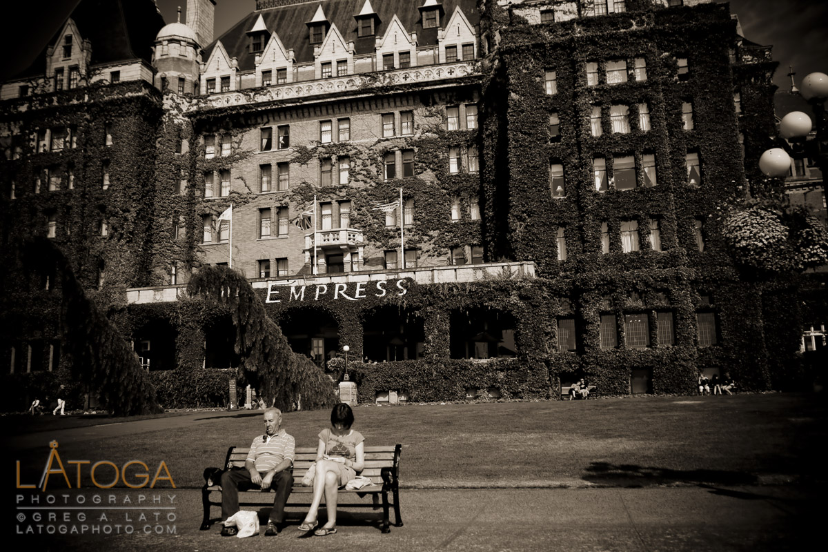 Two tourists rest on a park bench in front of the Empress Hotel in Victoria, BC.