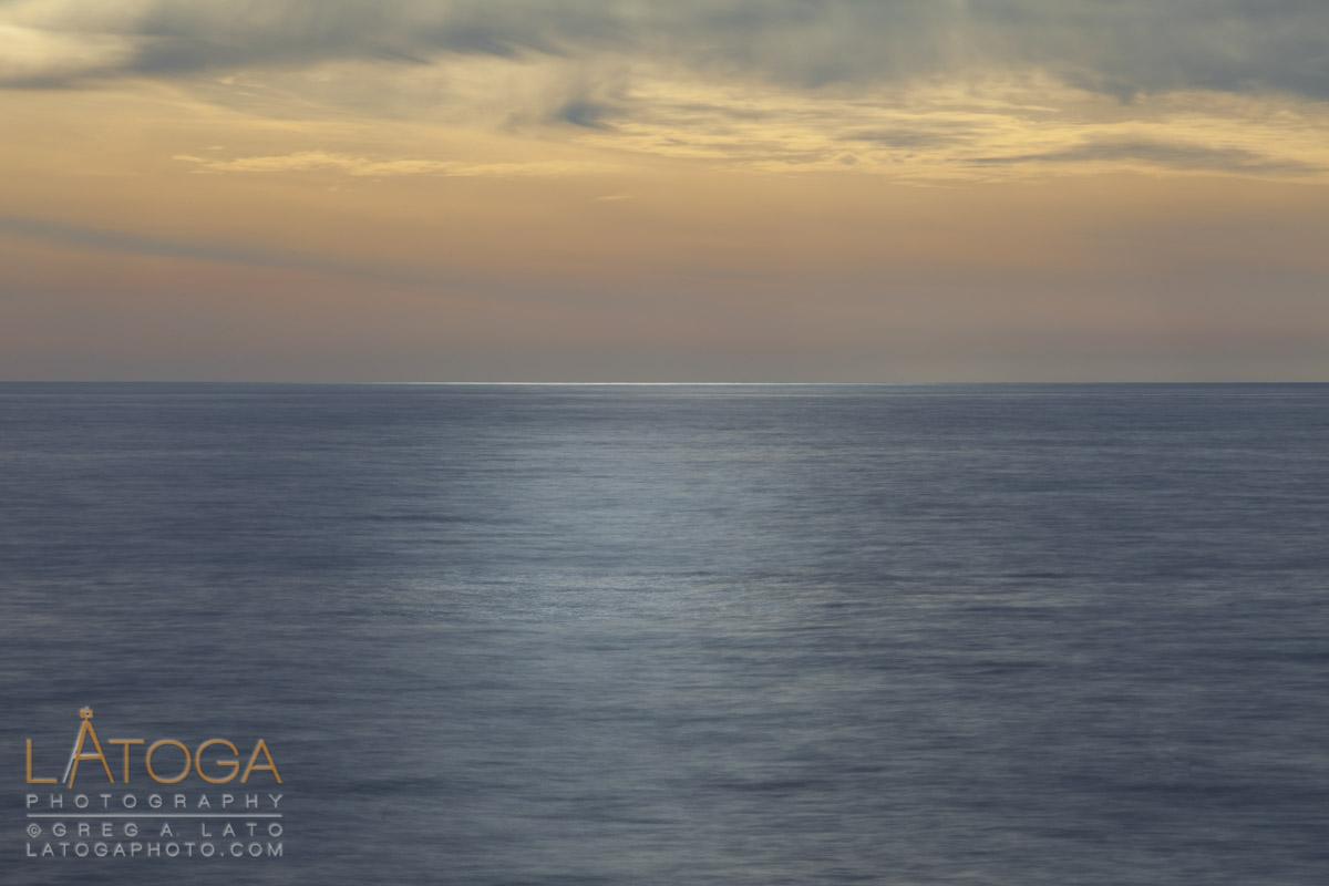 Sun highlights Pacific Ocean at sunset from Davenport, California.