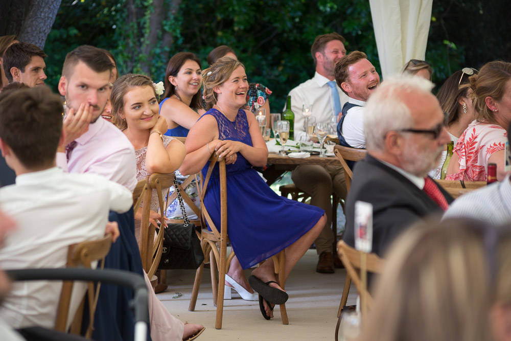 Guests laugh during best man's speech at Tros Yr Afon wedding venue, DIY Beaumaris castle wedding