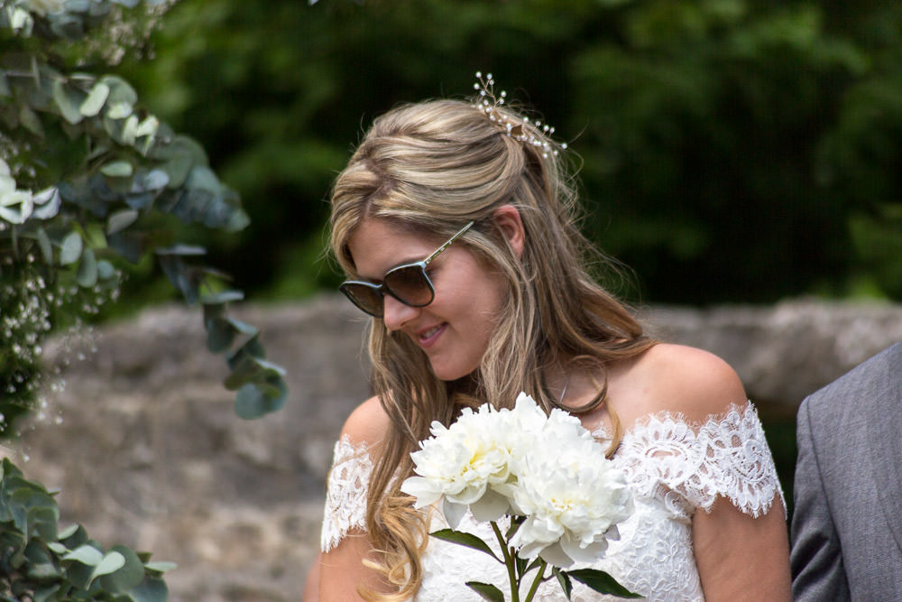 Bride smiling during humanist ceremony at Castle Aberlleiniog DIY Beaumaris castle wedding