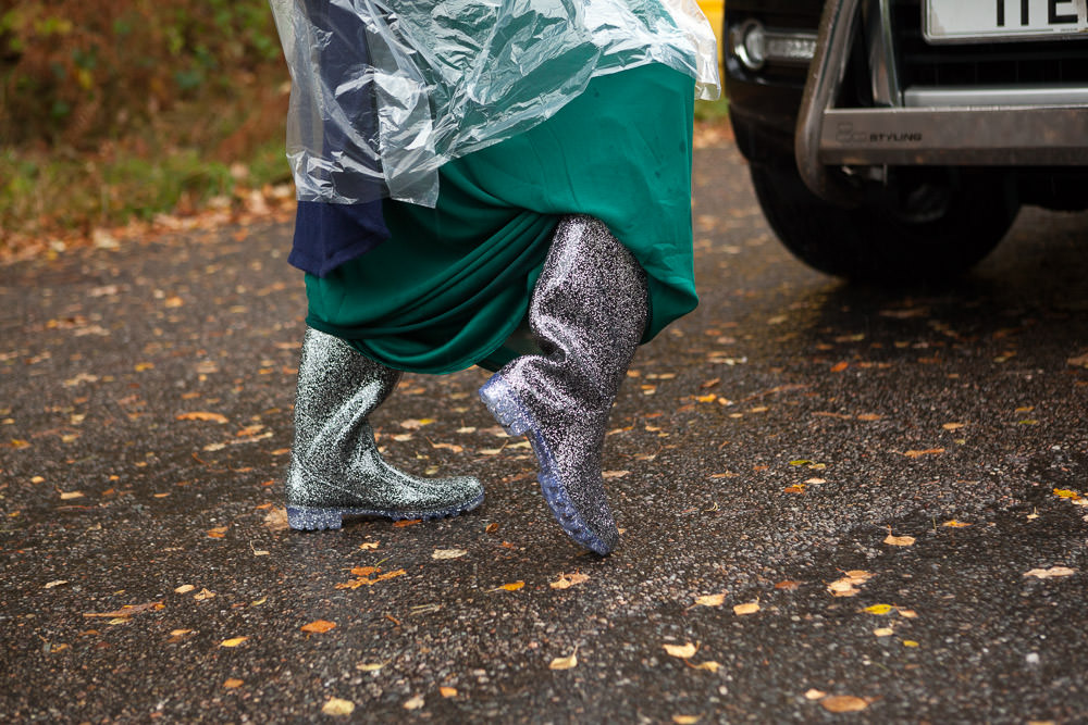 bridesmaid shows off her glitter wellies wedding guests walk down to the beach ceremony at Isle of Skye Wedding