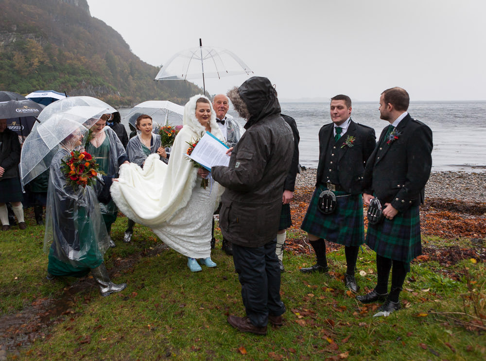 bridal party and guests in the rain during ceremony bridal party led by a piper down to the beach ceremony at Isle of Skye wedding