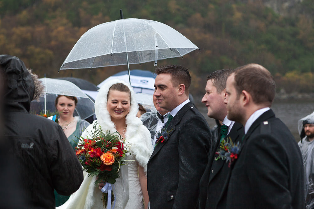 bride smiling in the rain during her outdoor wedding ceremony