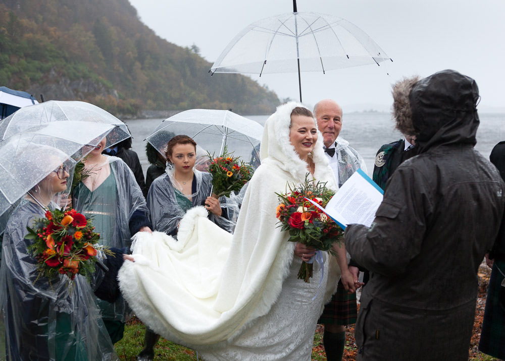 braidsmaids hold brides cloak out the dirt during beach ceremony