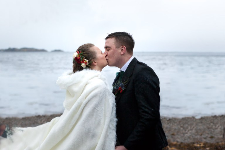 Bride and groom share first kiis at their beach ceremony at Isle of Skye Wedding