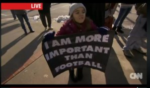 Young girl holding a sign that reads: I am more important than football