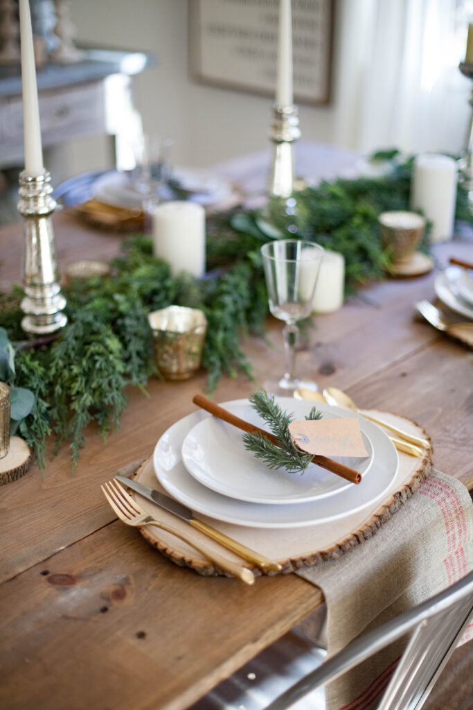 Bookmark this! A beautiful farmhouse Christmas tablescape with rustic elements, mixed metals, and natural greenery. Perfect for a hosting a holiday dinner!