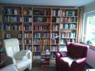 Im Bücherregal gibt es eine breite Literaturauswahl. Die gemütlichen Sessel laden zum Lesen und Relaxen ein.