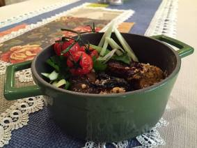 """Пълнени червени пиперки с мус от бял боб, ароматни билки, студено пресован зехтин и маслини, гарнирани с доматен сос със сушена манатарка, праз лук и печени орехи в тенджерка """"Lava"""""""