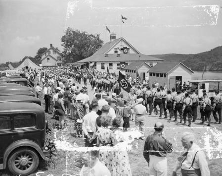 (Original Caption) 07/19/1937-Andover, N.J.: MILITARY PARADE AT NAZI CAMP OPENING. With American flags and Nazi Swastikas fluttering side by side, a Company of Ordnung Dienst, Nazi Military Police, is shown on parade at the opening of the Camp Norgeland at Andover,N.J.. Hitler and Il LDuce Mussolini were lauded to the skies in the speech making, while John Llewelyn Lewis, C.I.O. head, was called in effect a Communist organizer. The camp is operated by the German-American Bund.