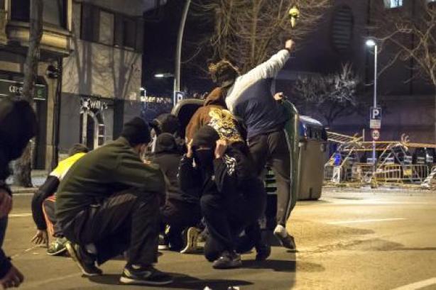 Manifestantes tras la marcha en apoyo al rapero Pablo Hasel se protegen de los Mossos d'Esquadra antidisturbios en Girona