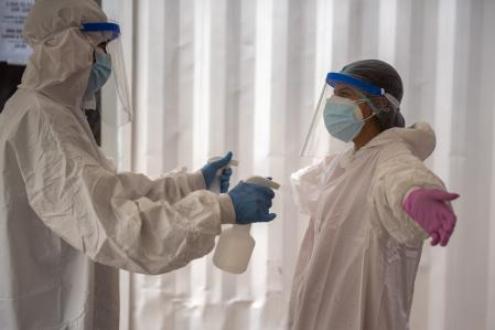 Healthcare worker disinfects a teammate after testing a person for COVID-19 in Montevideo, Uruguay, Thursday, April 15, 2021. (AP Photo/Matilde Campodonico)