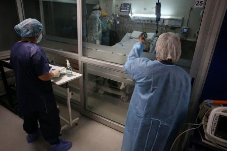 ACOMPAÑA CRÓNICA: URUGUAY CORONAVIRUS - AME081. MONTEVIDEO (URUGUAY), 15/04/2021.- Enfermeros del Centro de Tratamientos intensivos (CTI) del hospital privado Casmu atienden a pacientes covid-19, el 14 de abril de 2021 en Montevideo (Uruguay). El silencio ensordecedor, el aislamiento, la soledad y los últimos impulsos por intentar evitar que se escape una vida más. Esta es la rutina de las últimas semanas para los trabajadores de cuidados intensivos en el Casmu, uno de los hospitales privados de Uruguay. El impactante relato de ese personal sanitario, que lucha a diario por que la respiración artificial que reciben sus pacientes no sea la última de sus vidas, se ve en los pasillos y sectores de cuidados intensivos (CTI) de este hospital al que tuvo acceso Efe. EFE/ Raúl Martínez