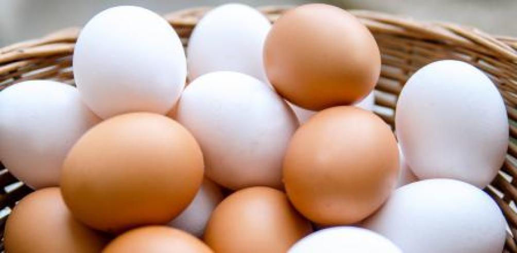 Huevos blancos y marrones en una cesta de mimbre