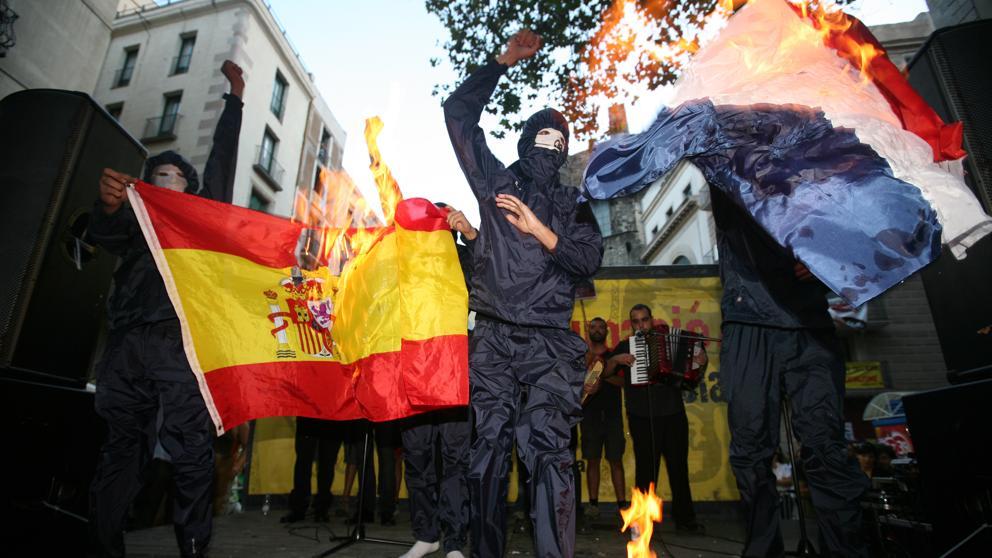 La manifestación de la izquierda independentista de la Diada reune a más de 5.000 personas. Al final de la marcha un grupo de encapuchados quemó banderas y fotografías del Rey. (Xavier Gómez)
