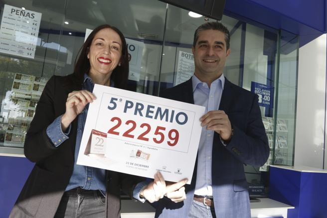 The owner of the lottery administration number 3 in Aguadulce, Roquetas de Mar neighborhood (Almería), Juan José Rodero, together with the employee Belén Ortíz, hold the poster with the number 22,259 awarded with a fifth prize in the Christmas Draw. EFE / Carlos Barba