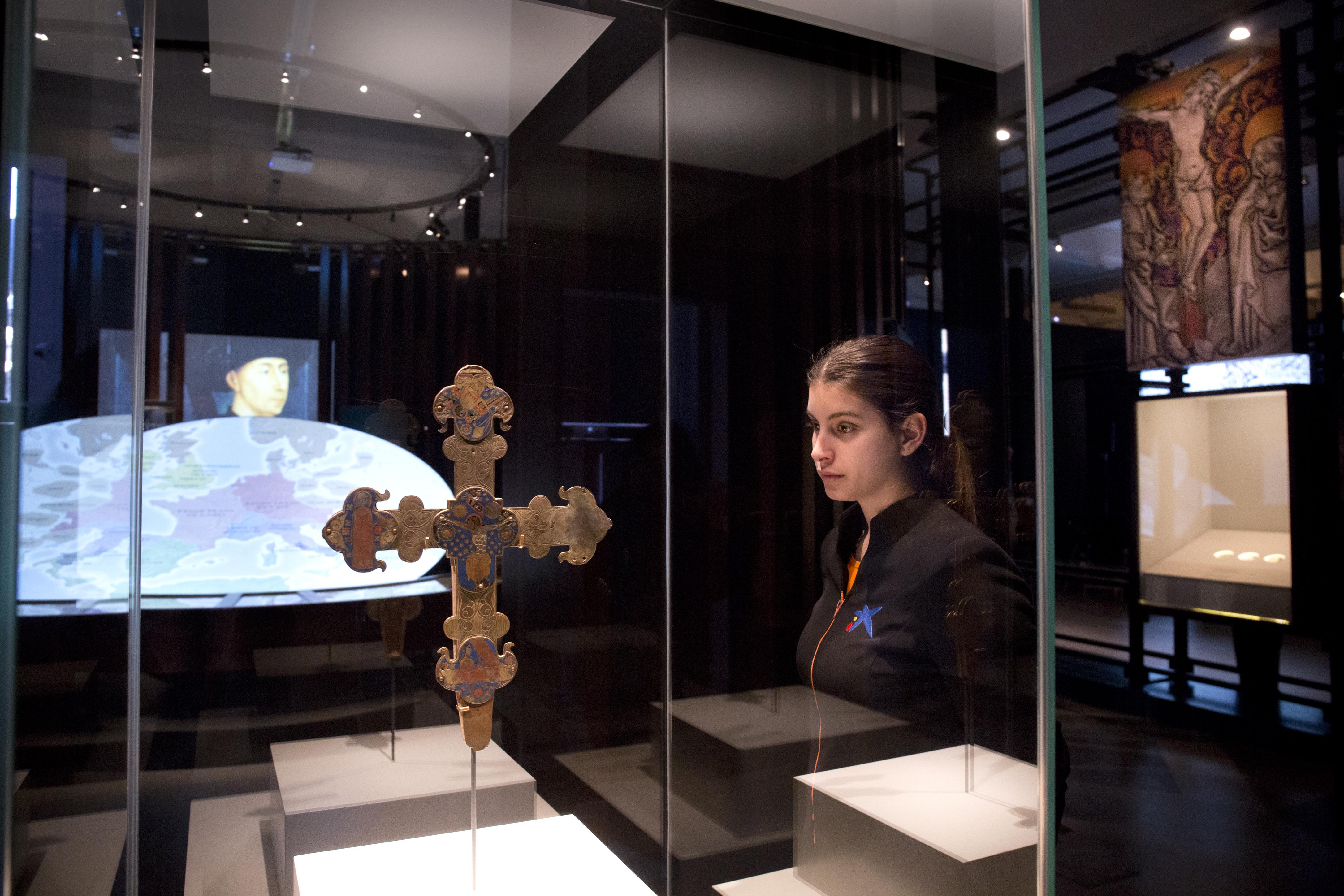 Una visitante observa una cruz medieval de la exposición  'Los pilares de Europa'