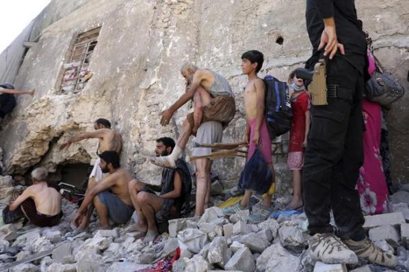 Un grupo de desplazados huyen sin ropa de sus hogares con motivo de la batalla entre las fuerzas iraquíes y el Estado Islámico (EI) en el casco antiguo de Mosul