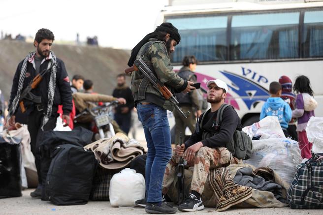 Los combatientes rebeldes y sus familias son vistos a su llegada al pueblo de Qalaat al-Madiq en la provincia de Hama