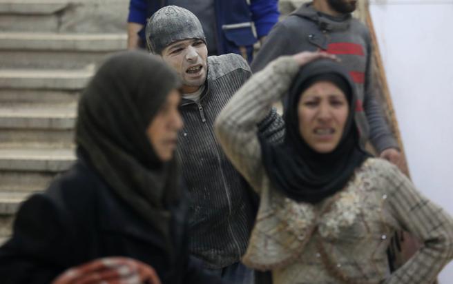 Ciudadanos sirios llegan a una clínica improvisada durante los ataques aéreos del gobierno sirio en Zamalka este martes