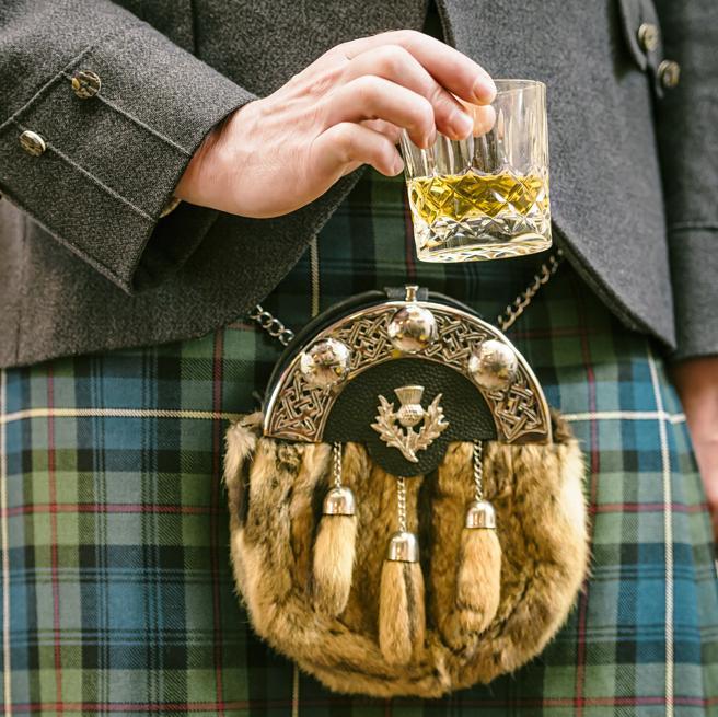 Hombre con kilt y un whisky