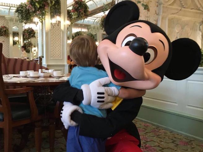 Un niño abrazando a Mickey