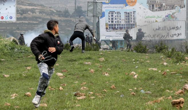 Varios palestinos lanzan piedras durante los enfrentamientos con soldados israelíes en la ciudad cisjordana de Ramala