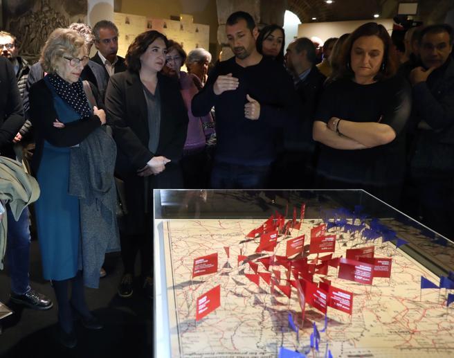La alcaldesa de Madrid, Manuela Carmena (i), y de Barcelona, Ada Colau (2i), junto a una maqueta de la exposición