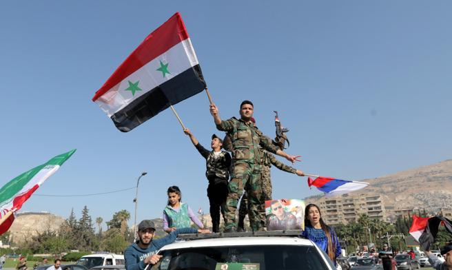 Protestas en apoyo a Asad en Damasco com banderas sirias, iraníes y rusas