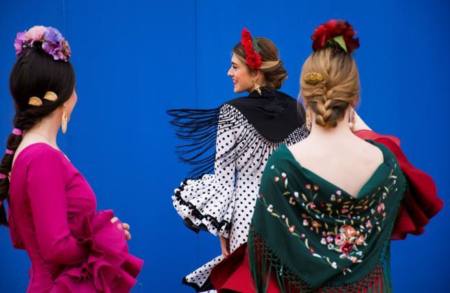 Tres asistentes de la Feria posan en una calles de Sevilla con sus tradicionales trajes