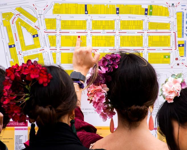 Asistentes de la Feria observa un mapa del Real, donde se asientan las casetas y se producen los tablaos y los restaurantes que reparten comida tradicional