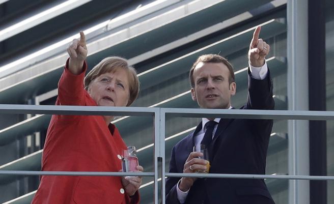 Merkel y Macron señalan hacia algún lugar de Berlín desde el balcón de la oficina de la canciller