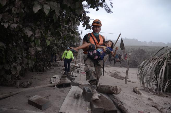 Un trabajador de los equipos de rescate de Guatemala ayuda a una niña en El Rodeo, Escuintla (Guatemala)