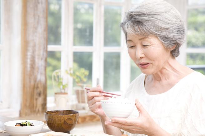 Mujer mayor comiendo arroz