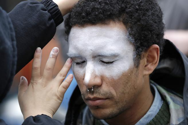 A man paints his face as a symbol of protest against facial recognition in October 2018